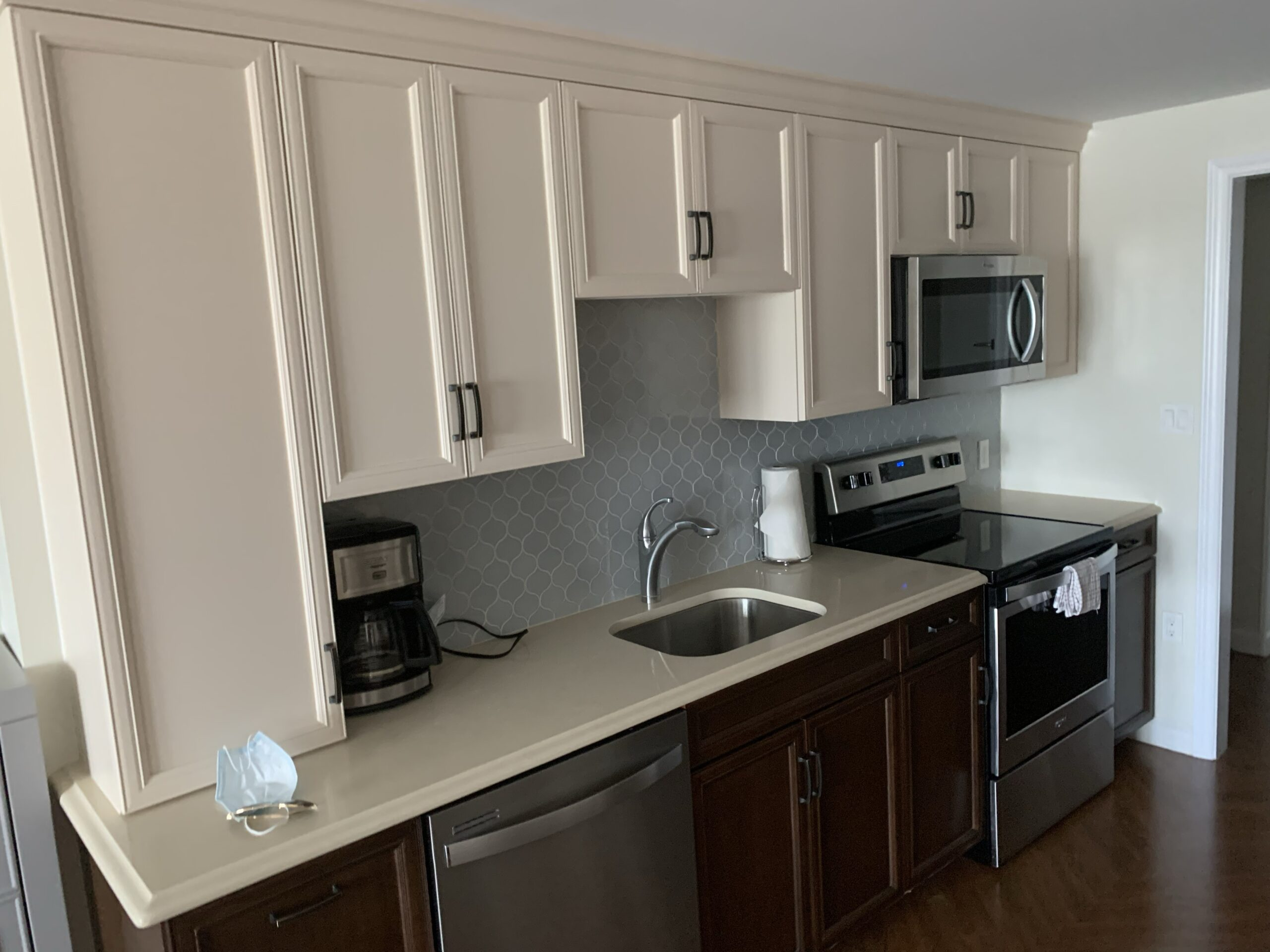 kitchen with beige countertop and hanging cabinets and dark brown under the sink storage