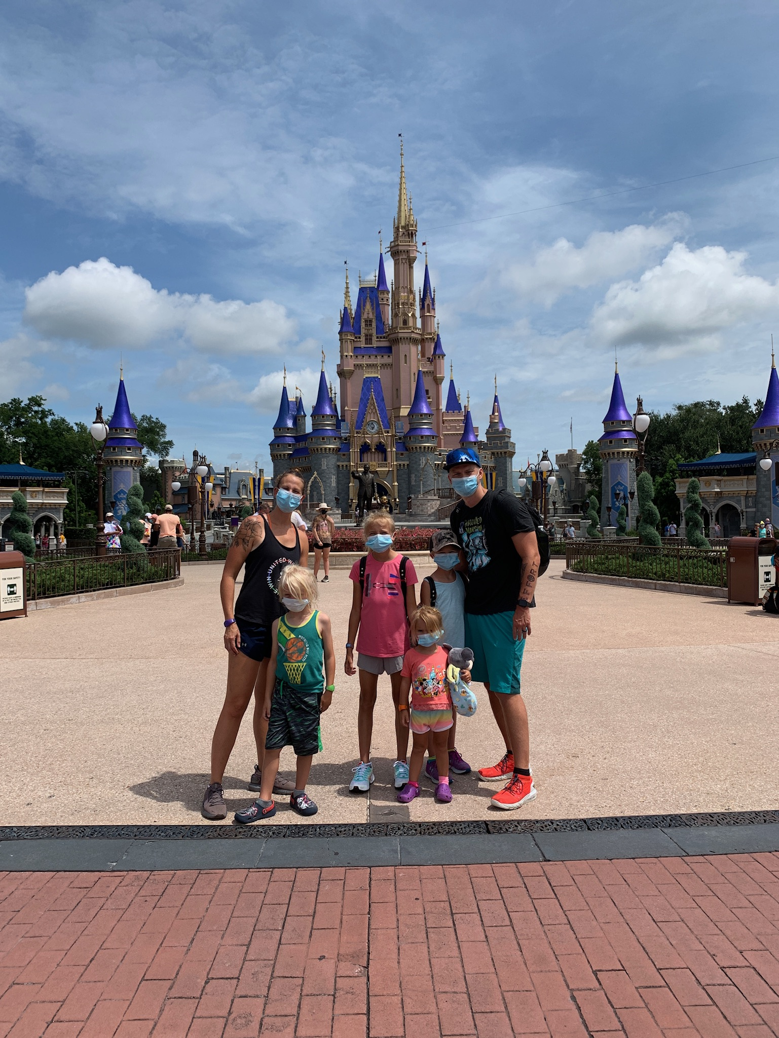 Mom, Dad, and four kids in front of the castle at Disney World